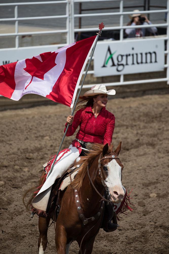 Cowgirl rider med Kanadas flagga på Calgary Stampede.