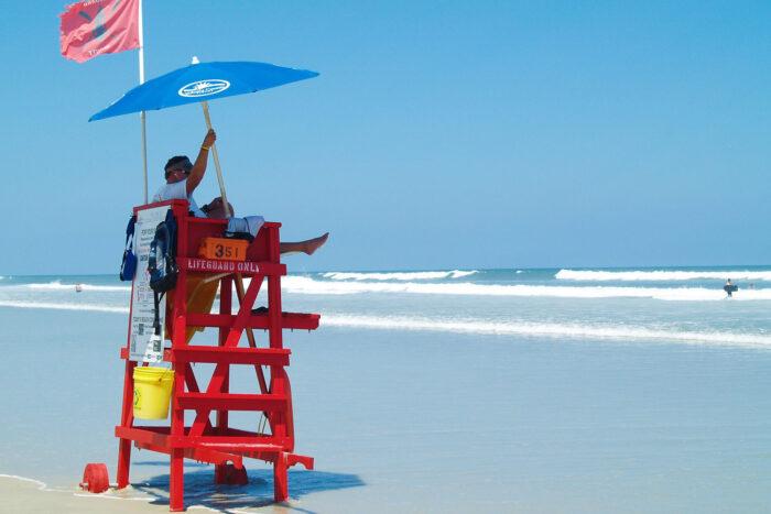 Badvakt sitter i torn och ser ut över havet i Daytona Beach.