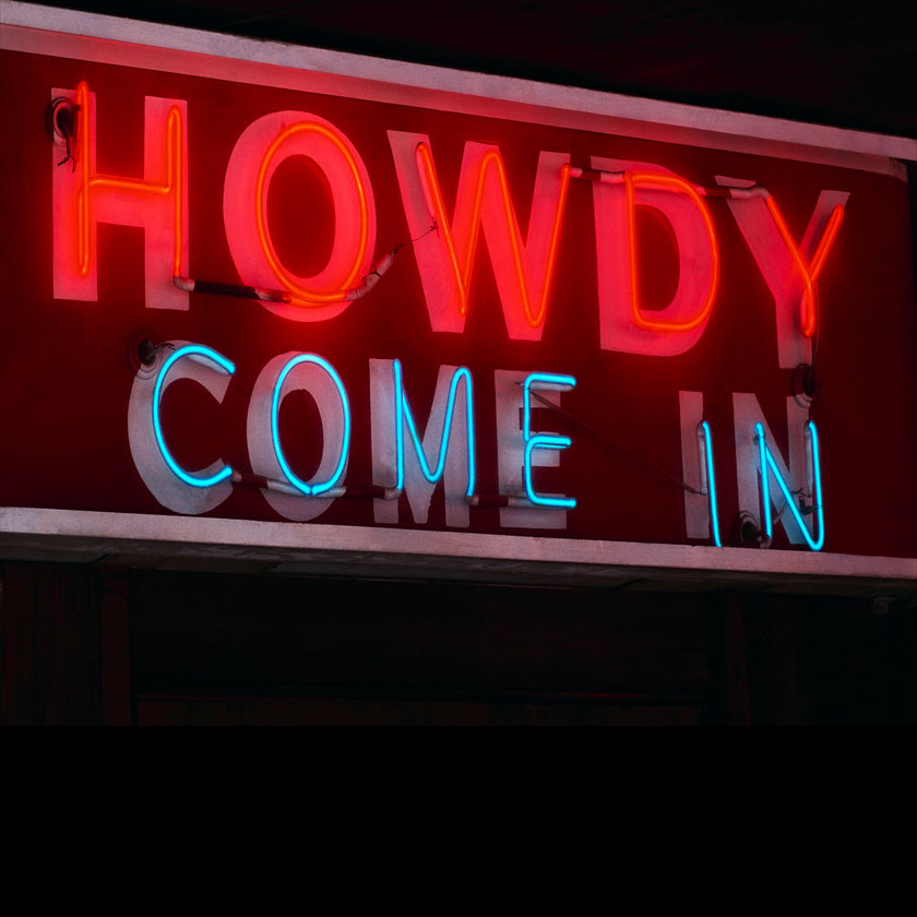 Neonskylt med texten Howdy Come In.
